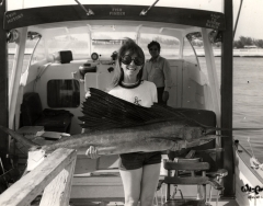 A woman hold a sailfish caught on the charter boat Osprey. Photo from the Wil-Art Stuido, gift of Angie Marine.